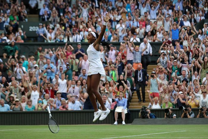 Coco Gauff jumps in the air with her hands held high.