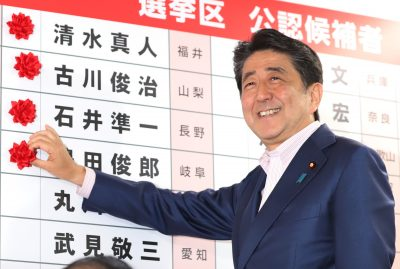Japanese Prime Minister and leader of the ruling Liberal Democratic Party (LDP) Shinzo Abe pins a rosette on the list of his party candidates in the Upper House election at the LDP headquarters in Tokyo on 21 July, 2019. (Reuters/ Photo by Yoshio Tsunoda/AFLO)