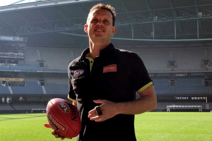 An umpire, wearing an AFL shirt and holding a football.