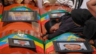 A woman lies on the coffin during a memorial service for the Ethiopian passengers and crew who perished in the Ethiopian Airways crash