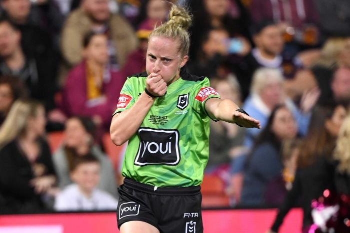 A female NRL referre blows a whistle in her right hand and points to the ground with an outstretched left arm.