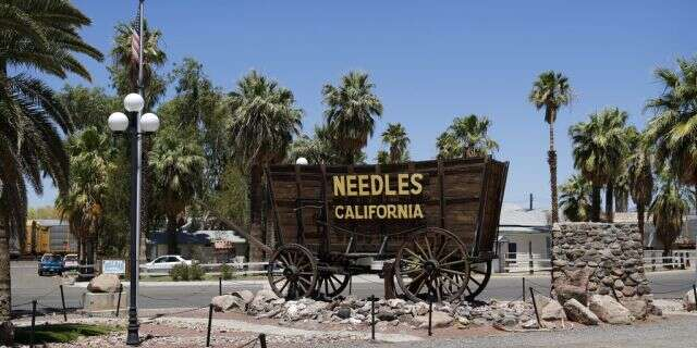 A sign adorns a historic wagon along old Route 66 in Needles, Calif. (Associated Press)