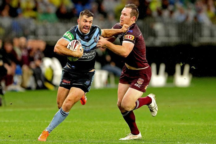 James Tedesco fends off Michael Morgan with the ball tucked under one arm