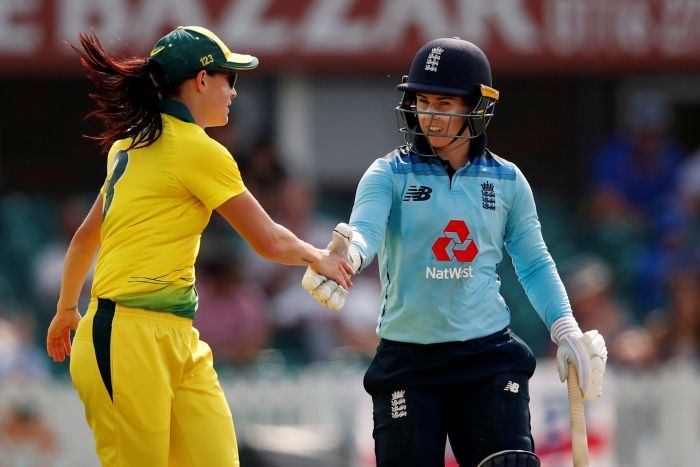Megan Schutt, wearing yellow, shakes hands with Tammy Beaumont, wearing blue