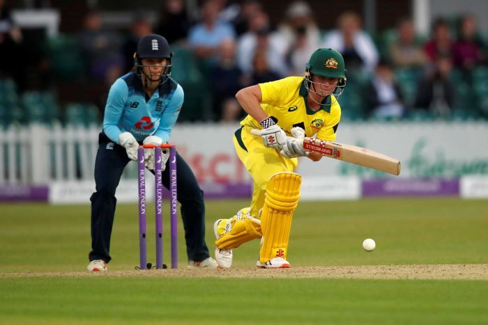 Beth Mooney hits a shot off the front foot as the England wicketkeeper watches on