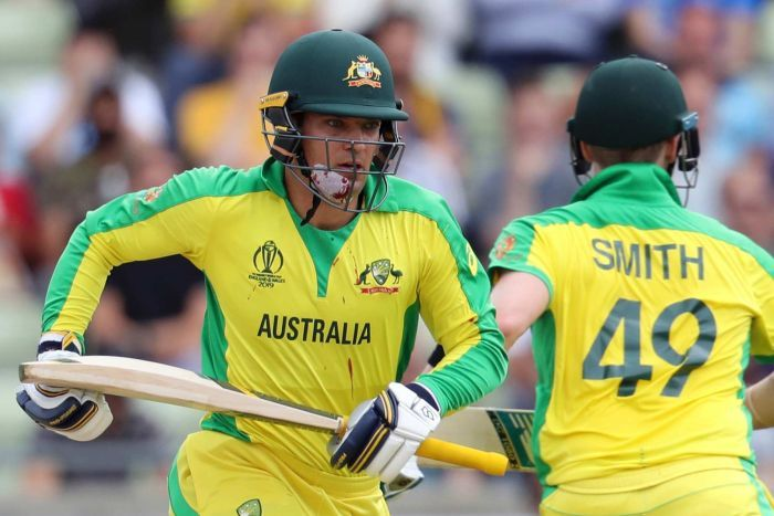 Alex Carey, with blood dripping from his bandaged chin to his shirt, runs with Steve Smith during a Cricket World Cup semi-final