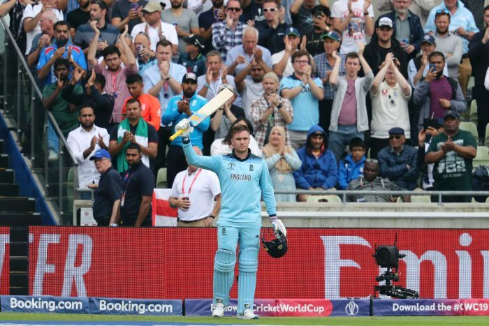 England batsman Jason Roy raises his bat and holds his helmet as cricket fans cheer behind him.