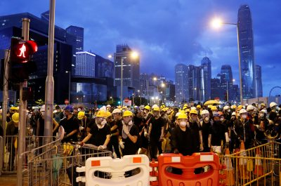 People stand behind a barricade during a demonstration near a flag raising ceremony for the anniversary of Hong Kong handover to China in Hong Kong, China, 1 July 2019. (Photo: Reuters/Tyrone Siu).