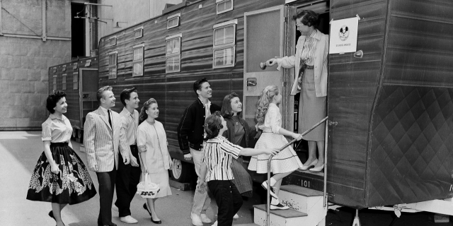 """In this Aug 20, 1957, file photo, Walt Disney's Mouseketeers enter a large trailer that serves as their school on the Disney lot in Hollywood, Calif. Greeting them is their teacher Jean Seaman of the Los Angeles Public School System. Jimmy Dodd, red-haired and fortyish, is master of Mouseketeer ceremonies. Mouseketeer Annette Funicello can be seen at far left. Police have confirmed that a body found in April 2019 at an Oregon home is that of missing man Dennis Day, who was an original member of Disney's """"The Mickey Mouse Club."""""""