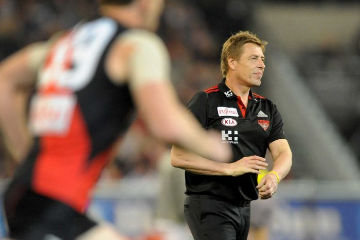 A blurred footballer runs through the frame in front of Mark Thompson on the MCG.