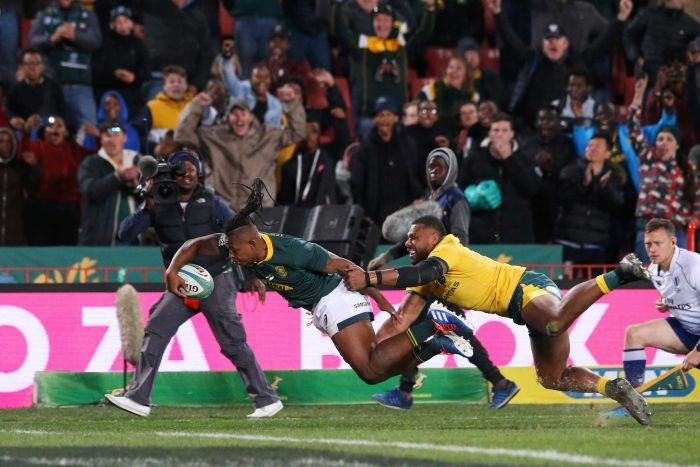 S'busiso Nkosi stretches to score a one-handed try as a Wallabies defender holds on