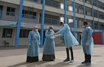 Palestinian health workers wearing protective facemasks go over instructions in the courtyard of a U.N. Relief and Works Agency for Palestinian Refugees school at the Al Shanti refugee camp in Gaza on March 18.
