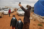 A Syrian woman wearing a protective face mask snaps a selfie in a camp for displaced people in Kafr Lusin, in the northwestern province of Idlib on March 18.