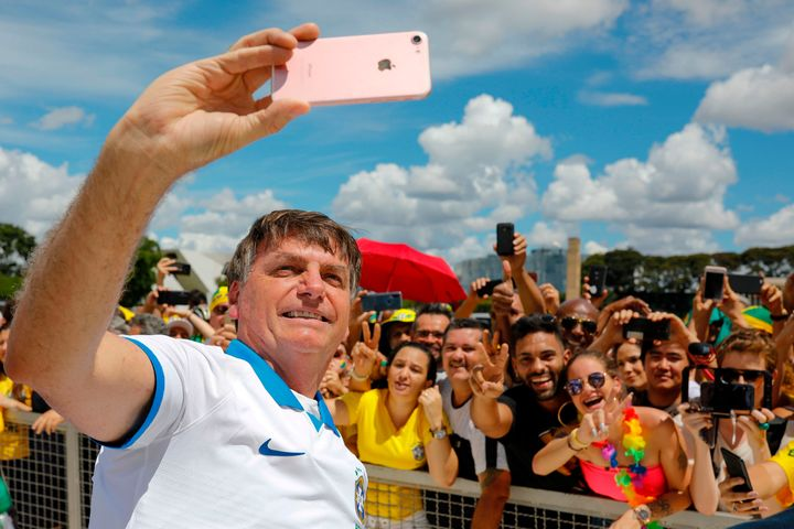 Brazilian President Jair Bolsonaro takes a selfie with supporters in front of the Planalto Palace on March 15, 2020.