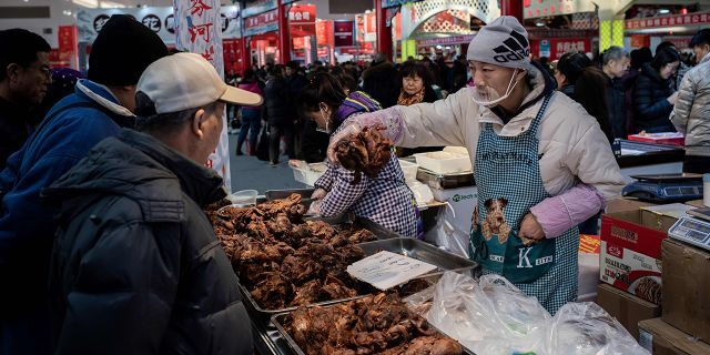 A vendor sells meat to customers at a market in Beijing on Jan. 15.