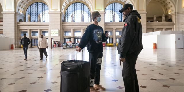 A traveler talks with a security officer at Washington Union Station, a major transportation hub in the nation's capital, Monday, March 16, 2020. The train station was nearly empty during morning rush hour as many government and private sector workers stay home during the coronavirus outbreak.