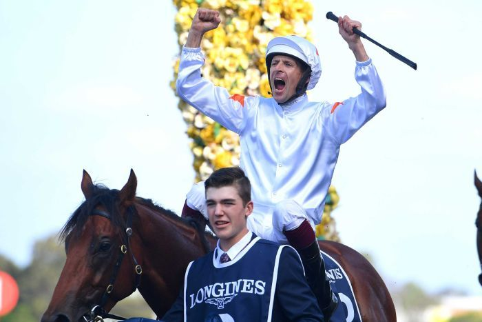 A jockey pumps both his fists as sits on top of a horse after riding it to victory in the Golden Slipper.