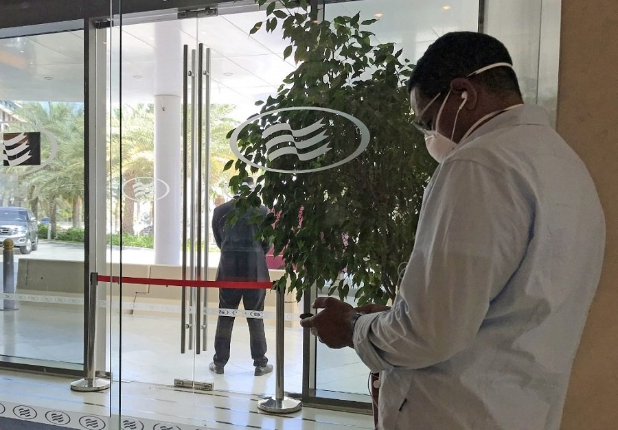 A mask-clad man uses his mobile phone while standing at the entrance of the Crowne Plaza hotel in Yas Island Abu Dhabi, where two Italian cyclists participating in the UAE Tour tested positive for COVID-19 coronavirus disease which prompted the cancellation of the cycling event, on February 28, 2020. (File/AFP)