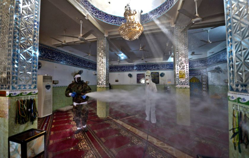 Civil defense workers in Iraq disinfect a mosque.