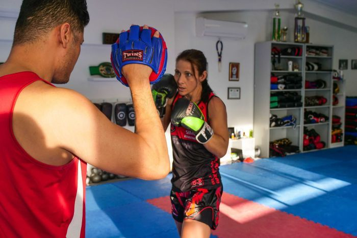 A man stand with his back to the camera holding up boxing pads while a woman wearing boxing gloves faces him ready to punch.