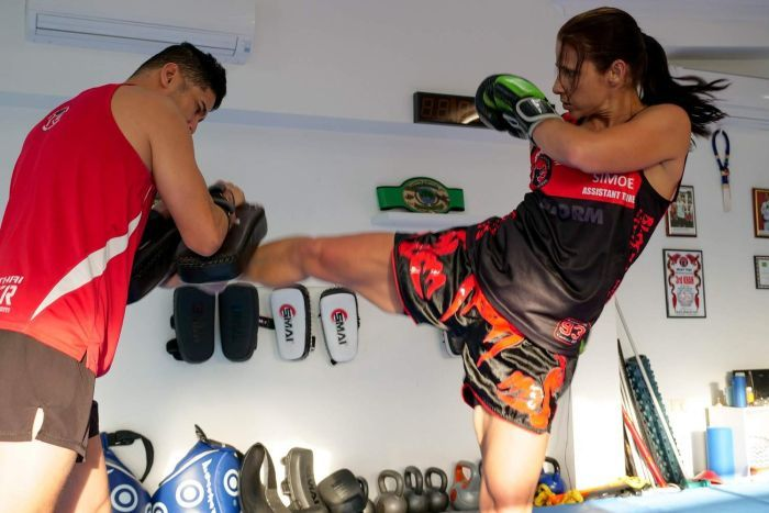 A woman kicks a punching pad while a man holds it.