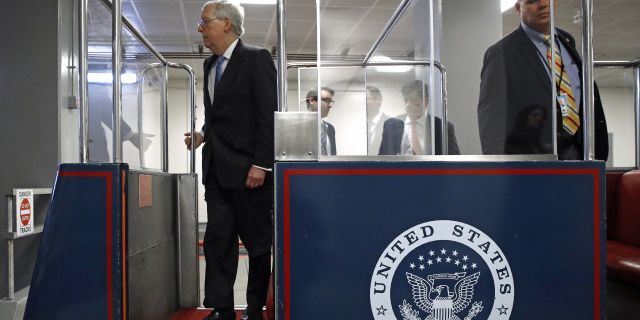 Senate Majority Leader Mitch McConnell of Ky., left, boards a subway car on Capitol Hill in Washington, Wednesday, March 18, 2020, before a vote on a coronavirus response bill. (AP Photo/Patrick Semansky)