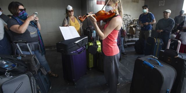 A traveler plays her violin prior to getting on a charter flight coordinated by the U.S. embassy at La Aurora airport in Guatemala City, Monday, March 23, 2020. American citizens stranded abroad because of the coronavirus pandemic are seeking help in returning to the United States. (AP Photo/Moises Castillo)
