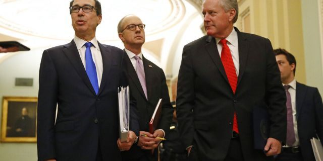 Treasury Secretary Steven Mnuchin, left, accompanied by White House Legislative Affairs Director Eric Ueland and acting White House chief of staff Mark Meadows, speaks with reporters as he walks to the offices of Senate Majority Leader Mitch McConnell of Ky. on Capitol Hill in Washington, Tuesday, March 24, 2020. (AP Photo/Patrick Semansky)
