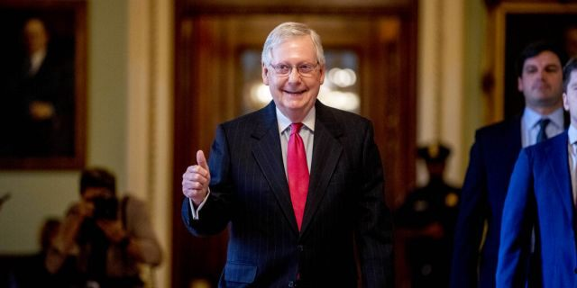 Senate Majority Leader Mitch McConnell of Ky. gives a thumbs up as he leaves the Senate chamber on Capitol Hill in Washington, Wednesday, March 25, 2020, where a deal has been reached on a coronavirus bill. The 2 trillion dollar stimulus bill is expected to be voted on in the Senate Wednesday. (AP Photo/Andrew Harnik)