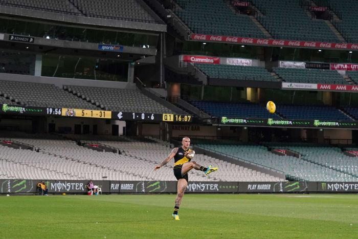 A male Richmond AFL player kicks the ball in front of an empty grandstand at the MCG.