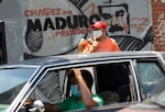 Maduro's face appears on a wall where a man waits in line Thursday to fill his car with gas in Caracas.