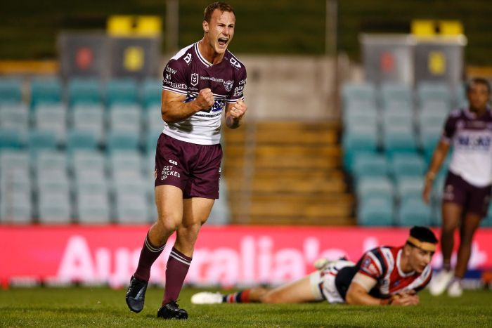 A Manly NRL player screams out and pumps his fists as he celebrates kicking the winning field goal against the Sydney Roosters.