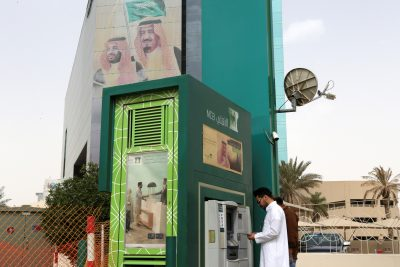 A man withdraws money from an ATM outside the Saudi National Commercial Bank (NCB), after an outbreak of coronavirus, in Riyadh, Saudi Arabia, 18 March 2020 (Photo:Reuters/Ahmed Yosri).