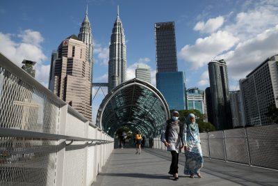 A woman wearing a protective face mask crosses a bridge, following the outbreak of the coronavirus in China, in Kuala Lumpur, Malaysia, 19 February 2020 (Photo: Reuters/Lim Huey Teng).