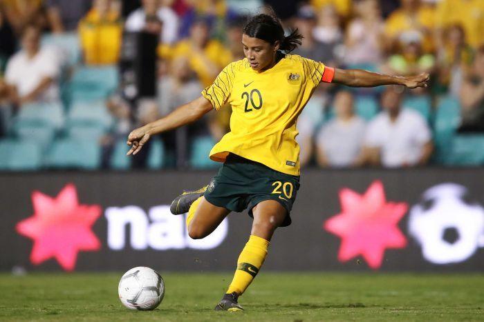 Sam Kerr wearing a yellow Matildas team shirt kicks a soccer ball on the turf of a sports arena.