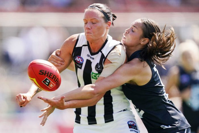 Stacey Livingstone gets a handball away while being tackled.