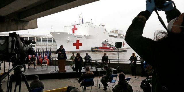 A journalist records speakers at a press briefing following the arrival of the USNS Comfort, a naval hospital ship with a 1,000 bed-capacity, March 30, 2020, at Pier 90 in New York. The ship will be used to treat patients who do not have the new coronavirus as land-based hospitals fill up to capacity with those that do.