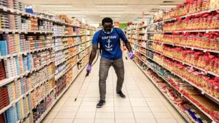 A man is disinfects a empty supermarket in Dakar on May 11, 2020. - Big supermarkets are being closed down on specific days for a few weeks in order to disinfect them against the spread of the COVID-19 coronavirus.