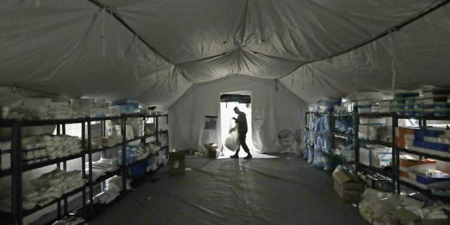 A U.S. Army soldier walking inside a mobile surgical unit being set up by soldiers from Fort Carson, Col., and Joint Base Lewis-McChord (JBLM), as part of a field hospital inside Seattle's CenturyLink Field Event Center this past March.