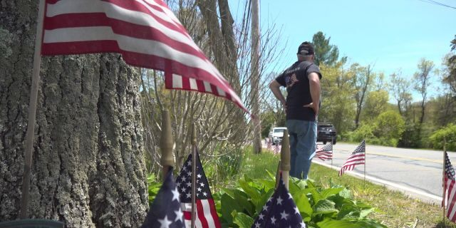 Paul Monti stands by his American flag display at his home in Raynham, Mass.