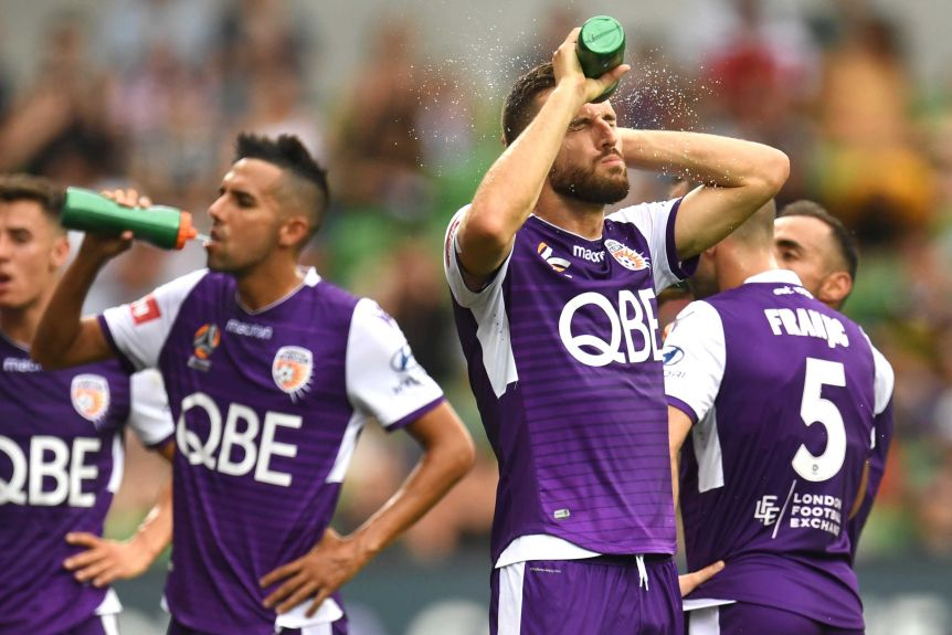Perth Glory players drink from water bottles and spray water on themselves.