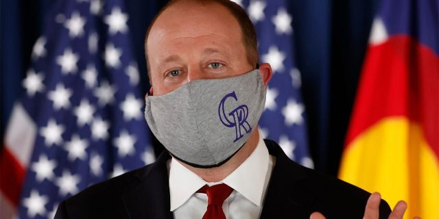 Colorado Governor Jared Polis makes a point while wearing a face mask with the logo of Major League Baseball's Colorado Rockies during a news conference to update the state's efforts to control the spread of the new coronavirus Friday, May 15, 2020, in the State Capitol in Denver.