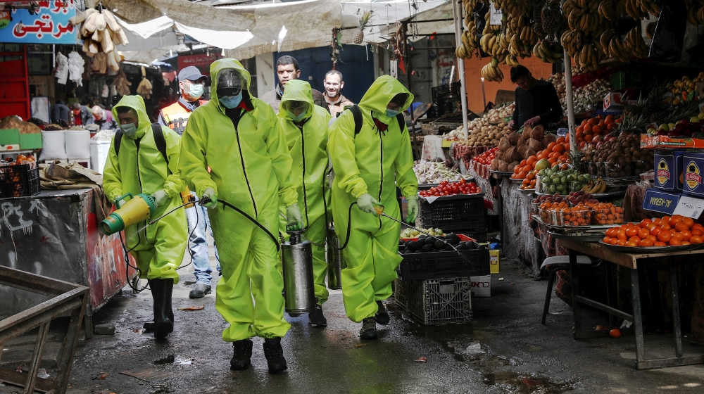 Workers wearing protective gear spray disinfectant as a precaution against the coronavirus, at the main market in Gaza City, Friday, March 27, 2020. Gaza municipality close all the weekly Friday marke
