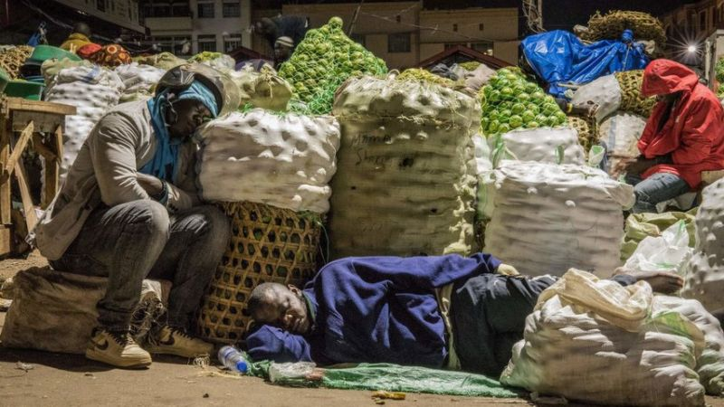 Traders sleep next to items to be sold at a market following a directive from Ugandan President Yoweri Museveni that all vendors should sleep in markets for 14 days to curb the spread of the COVID-19 coronavirus at Nakasero market in Kampala, Uganda, on April 7, 2020