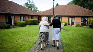Older lady and helper in residential care complex