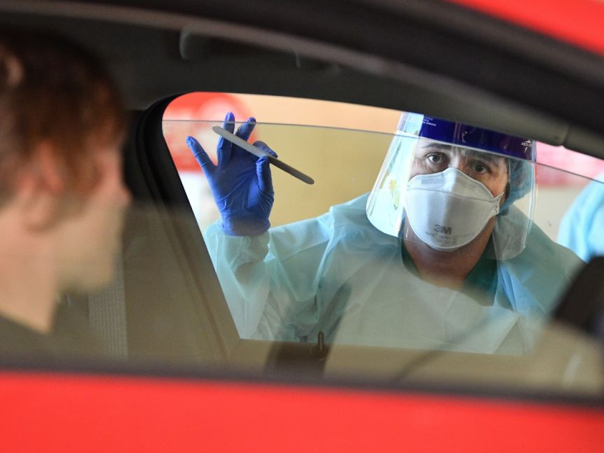 A person in bioprotective gear including mask, stands at a passenger side window holding a swab test.