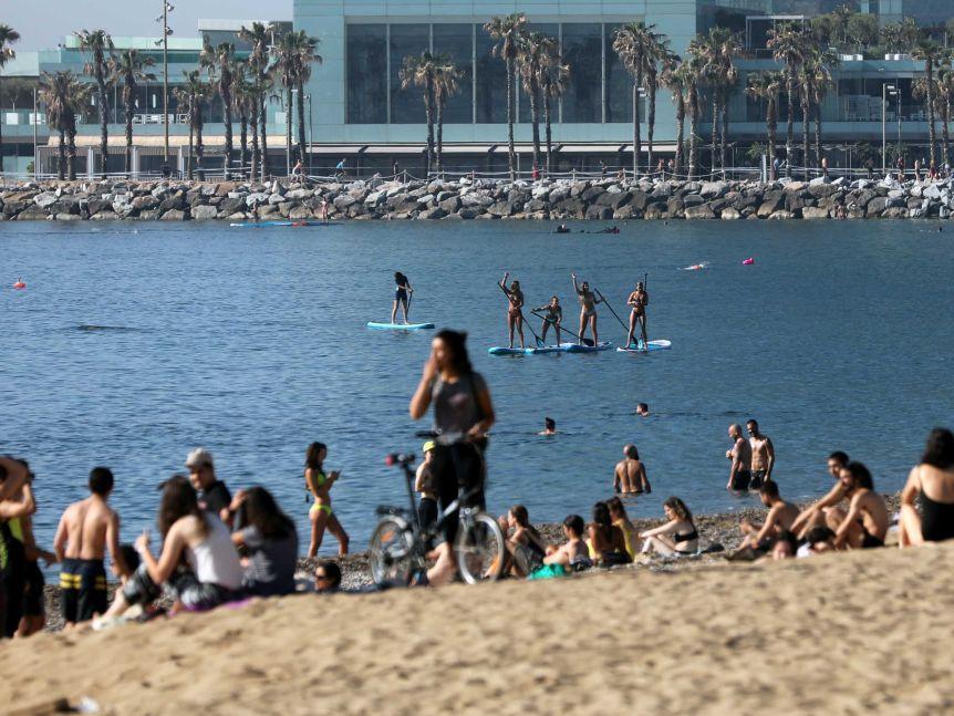 People practice paddle boarding at Barceloneta beach, amid the coronavirus disease (COVID-19) outbreak, in Barcelona.