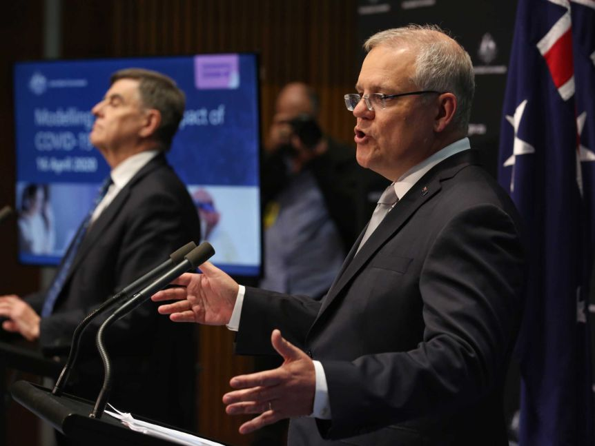 Scott Morrison in a suit and grey tie mid sentence standing next to the chief medical officer at a press conference.
