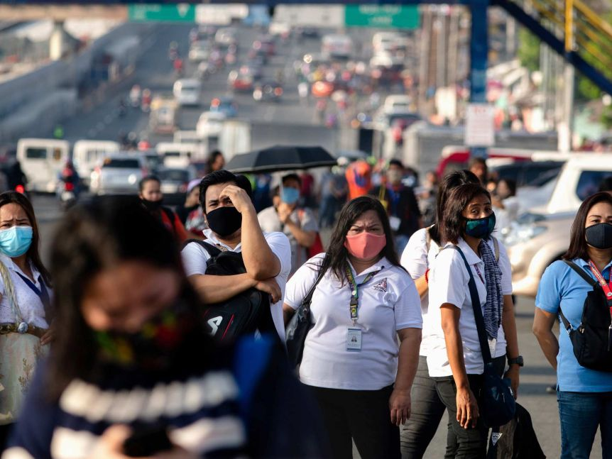 A group of people wearing face masks carry shoulder bags as they stand next to a large, busy road.