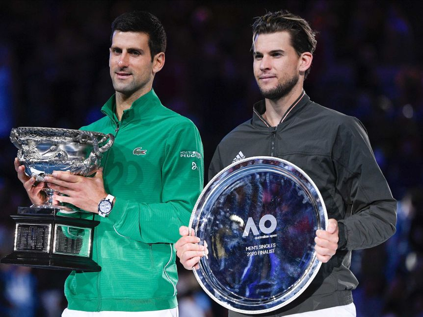 The two finalists in the Australian Open stand next to each other, one holding the winner's trophy.